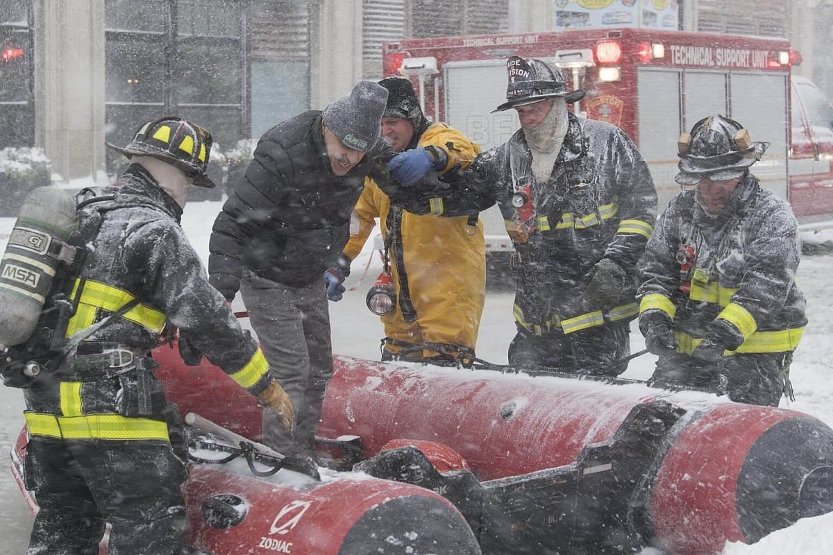 Firefighters help man out of a boat in Boston, on Jan 4, 2018.