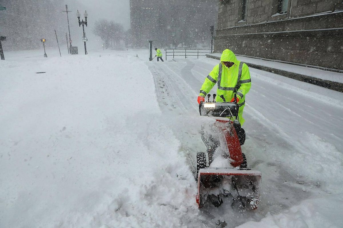 A city worker uses a snow blower to clear sidewalks as snow falls from a massive winter storm in Boston, on Jan 4, 2018.