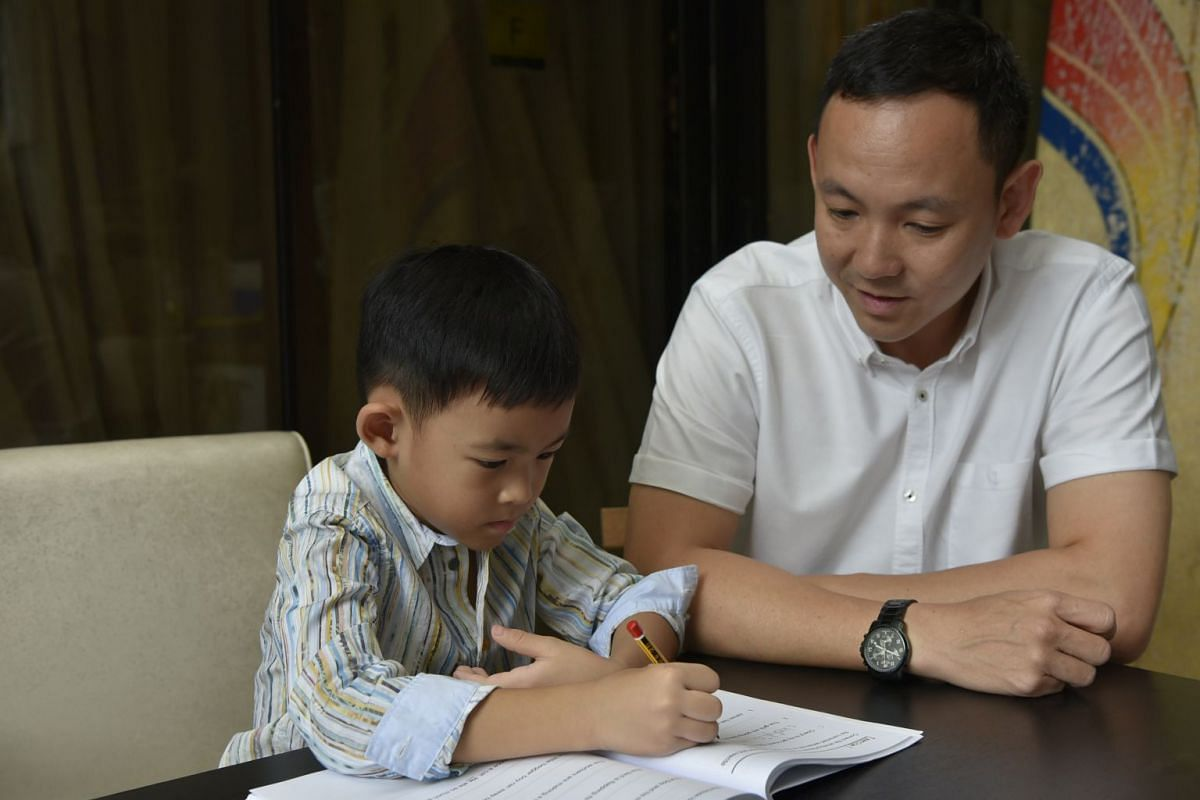Mr Bryan Tan sits with his son Michael as he does his homework.