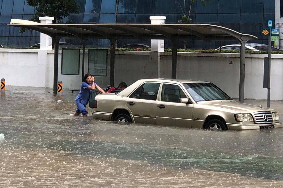 People pushing a car through floodwaters along Upper Changi Road on Jan 8, 2018.