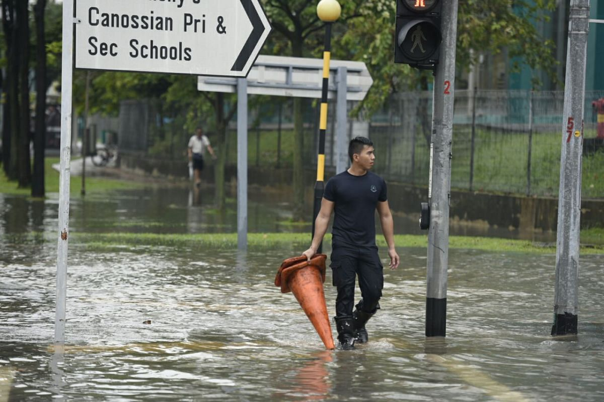 An SCDF officer from Changi Fire Station walking through the flooded junction between Upper Changi Road and Bedok North Avenue 4.