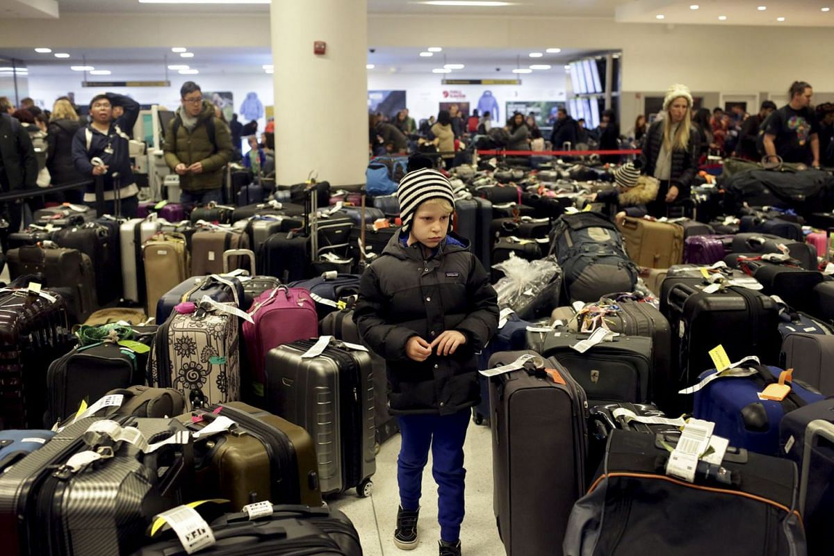 Passengers wade through a large collection of delayed bags at the arrivals hall of Terminal 4 at John F. Kennedy International Airport in New York, Jan. 7, 2018. PHOTO: THE NEW YORK TIMES