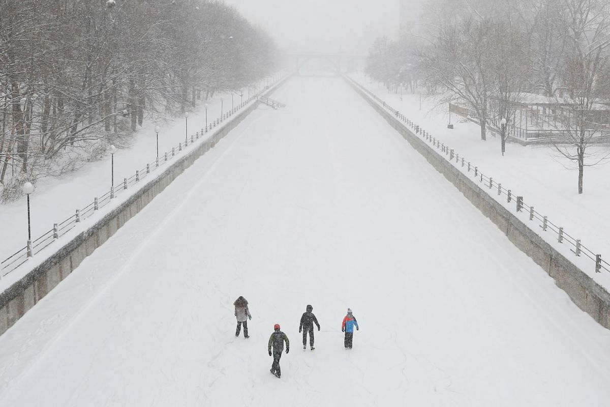 People skate on the Rideau Canal as snow falls in Ottawa, Ontario, Canada, January 8, 2018. PHOTO: REUTERS