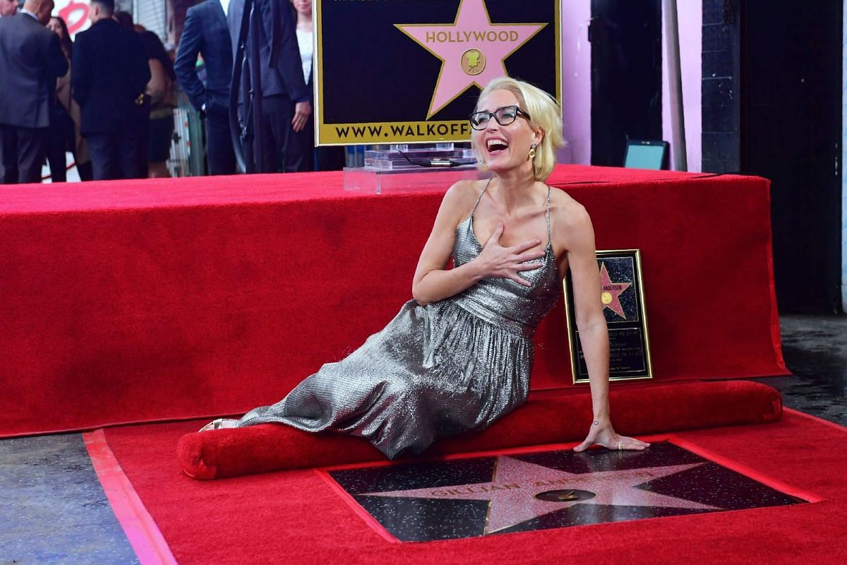 Actress Gillian Anderson poses on her Hollywood Walk of Fame Star in Hollywood, California on January 8, 2017, where she was the recipient of the 2,625th Star in the category of Television. PHOTO: AFP
