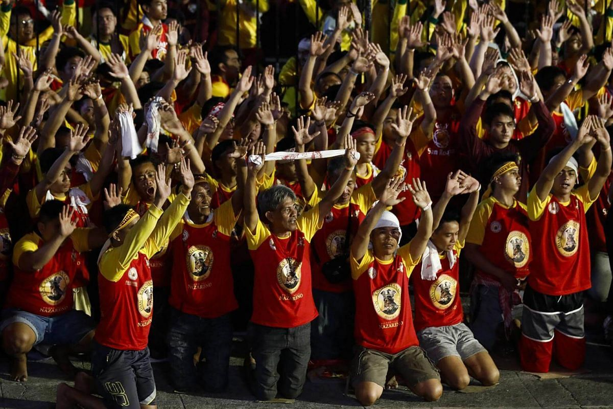 Catholic devotees kneel in praise of the Black Nazarene during a procession to mark its feast day in Manila, on Jan 9, 2018.