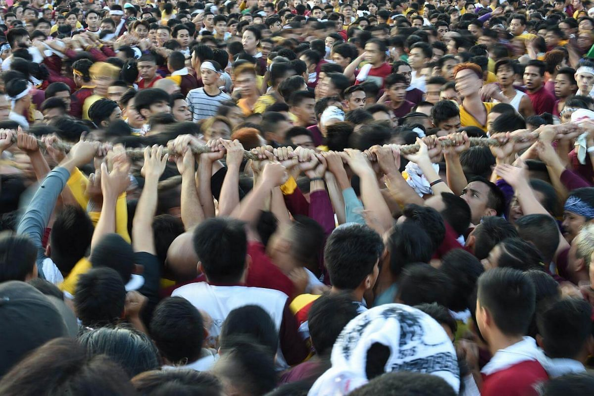 Devotees hold onto a rope connected to the carriage carrying the statue of the Black Nazarene during the annual religious procession in Manila, on Jan 9, 2018.