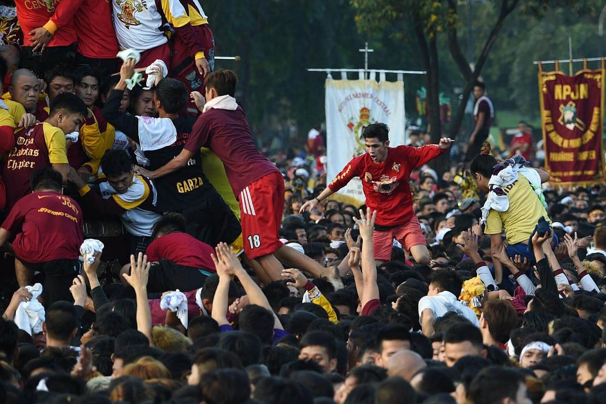 Devotees climb onto each other as they try to touch the statue of the Black Nazarene during the annual religious procession in Manila, on Jan 9, 2018.