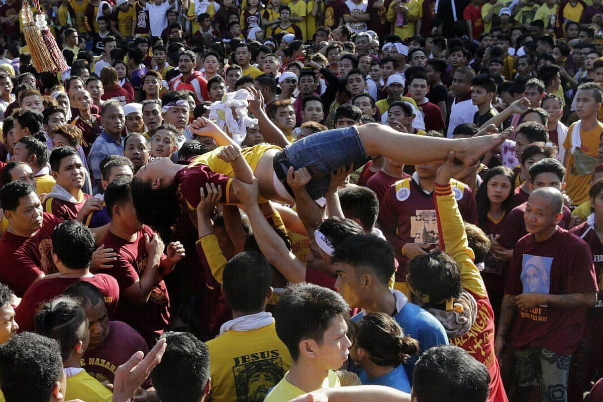 An unconscious lady is carried by Catholic devotees during a procession of The Black Nazarene to mark its feast day in Manila, on Jan 9, 2018.