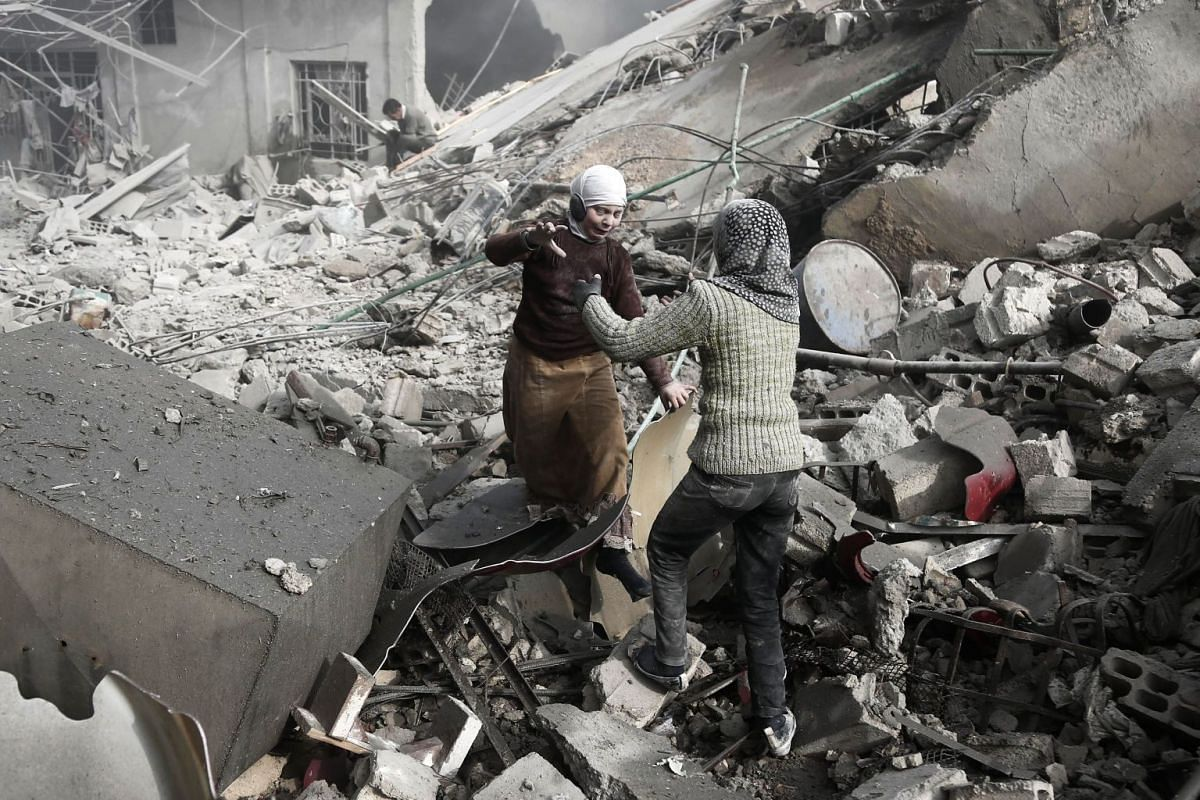Two Syrian sisters run across the rubble to embrace after finding each other alive following an air strike on Saqba, in the besieged rebel-held Eastern Ghouta area near Damascus, on January 9, 2018. PHOTO: AFP