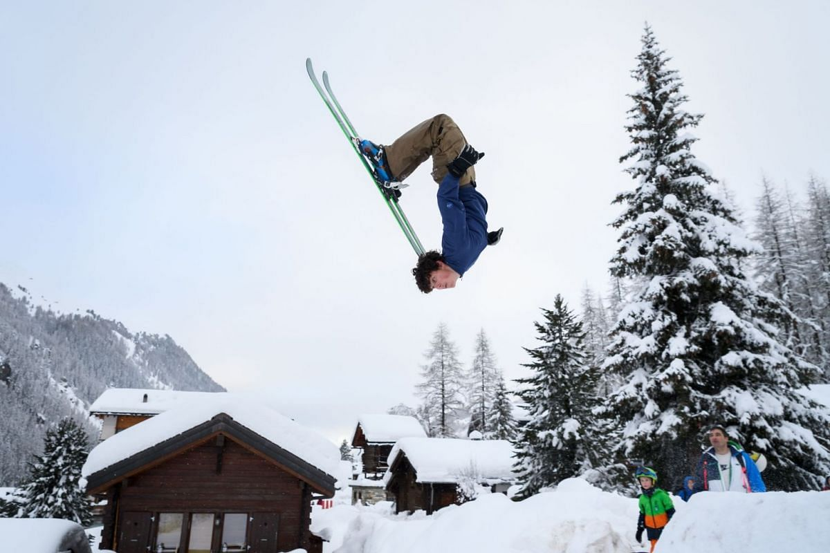 Teenager Luc makes a backflip on skis in the small resort of Zinal, Swiss Alps on January 9, 2018, after the access road which was cut by heavy snowfall reopened. PHOTO: AFP