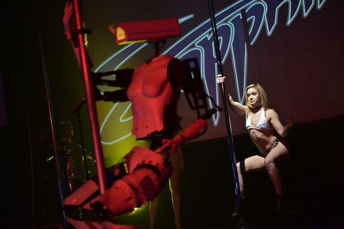 A human dancer performs next to a stripper robot at the Sapphire Gentlemen's Club on the sidelines of CES 2018 in Las Vegas on January 8, 2018. PHOTO: AFP
