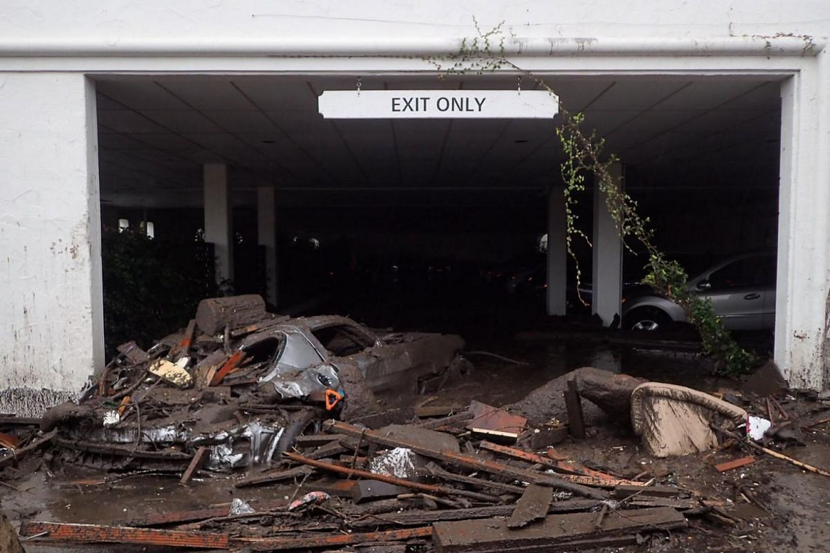 Damaged vehicles carried by mud flow and debris at the exit of a parking garage at the corner of Olive Mill and Coast Village Road following heavy rains in Montecito, California.