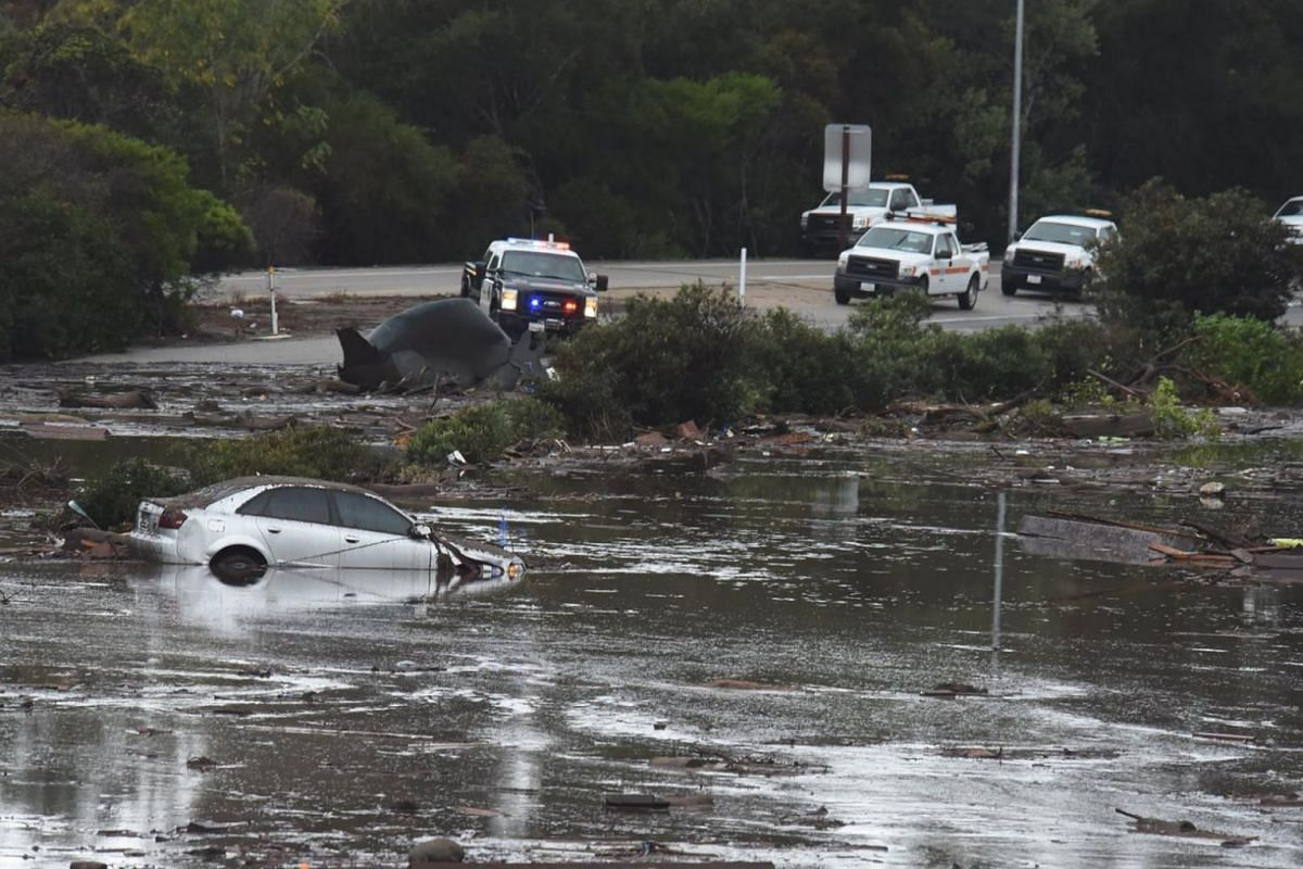 The US 101 Freeway at the Olive Mill Road overpass flooded with runoff water from Montecito Creek and blocked with mudflow and debris following heavy rains.