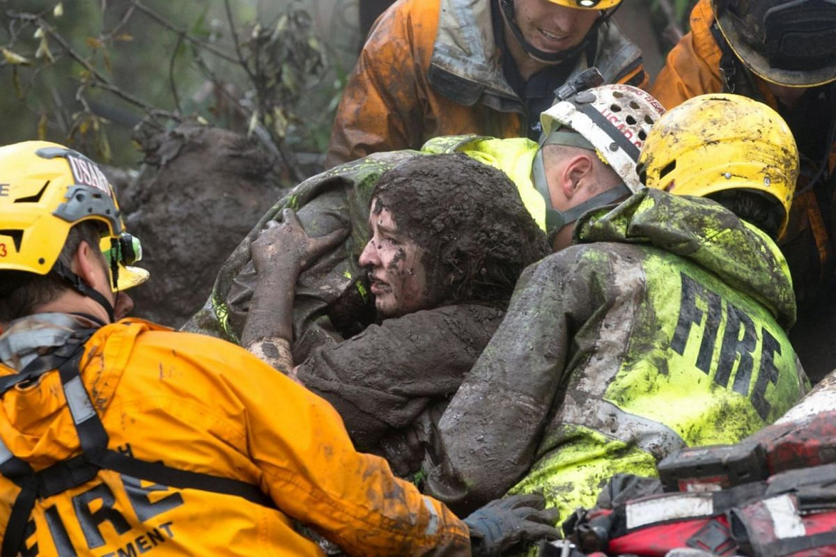 Emergency personnel carry a woman rescued from a collapsed house after the mudslide in Montecito, California.