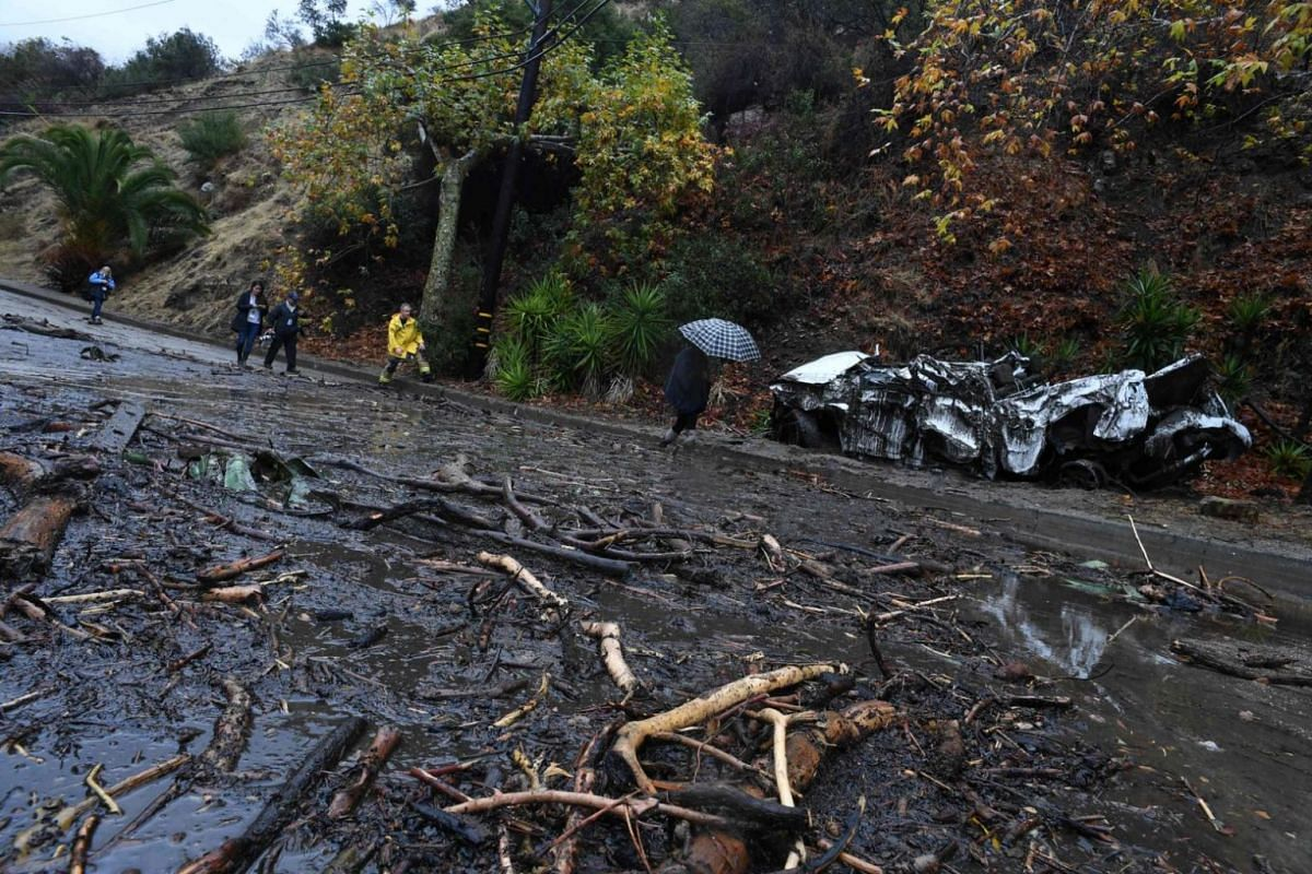 A firefighter (in yellow) instructs journalists to retreat to safer ground after a rain-driven mudslide destroyed two cars and damaged property in Burbank, California.