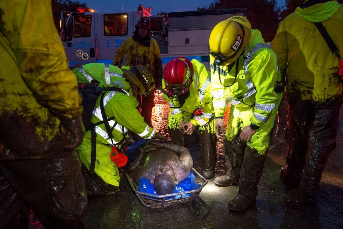 Emergency personnel carry a man covered in mud after a mudslide in Montecito, California.