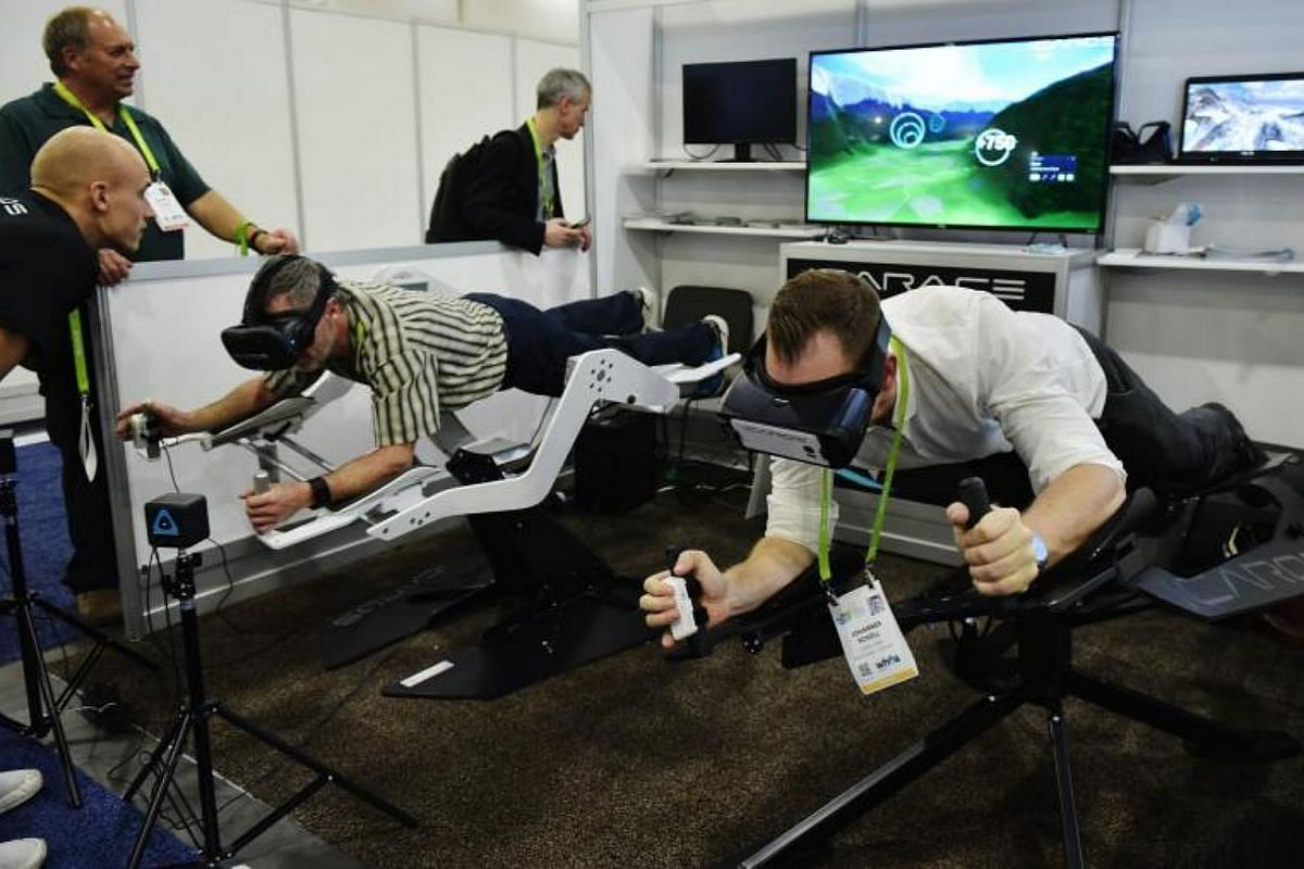 An exhibitor demonstrates the ICAROS virtual reality exercise machine at the Sands conventon hall during CES 2018 in Las Vegas on Jan 9, 2018.