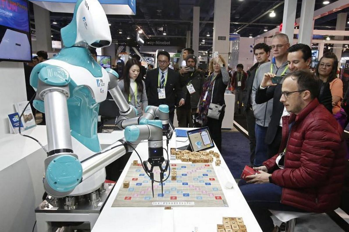 A man plays a game with a robot from ITRI, Industrial Technology Research Institute on opening day at the 2018 International Consumer Electronics Show in Las Vegas, Nevada, on Jan 9, 2018.