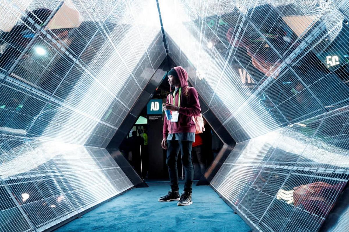 Jordan Jtakin walks though a 5G wireless broadband technology display in the Intel booth during the 2018 CES in Las Vegas, Nevada, on Jan 9, 2018.