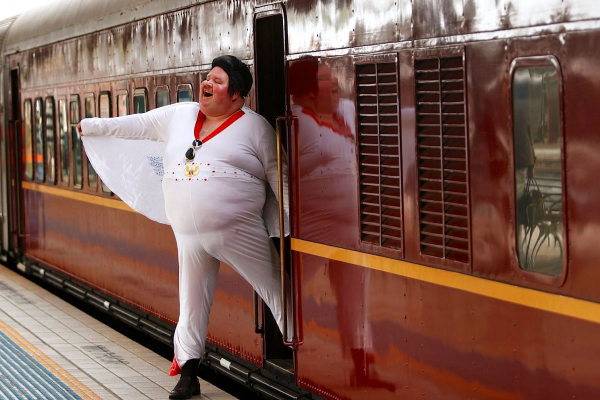 Elvis Presley impersonator Sean Wright poses next to the Elvis Express train at Sydney's Central station before it departs for the 26th annual Elvis Festival being held in the New South Wales town of Parkes in Australia, January 11, 2018. PHOTO: REUT