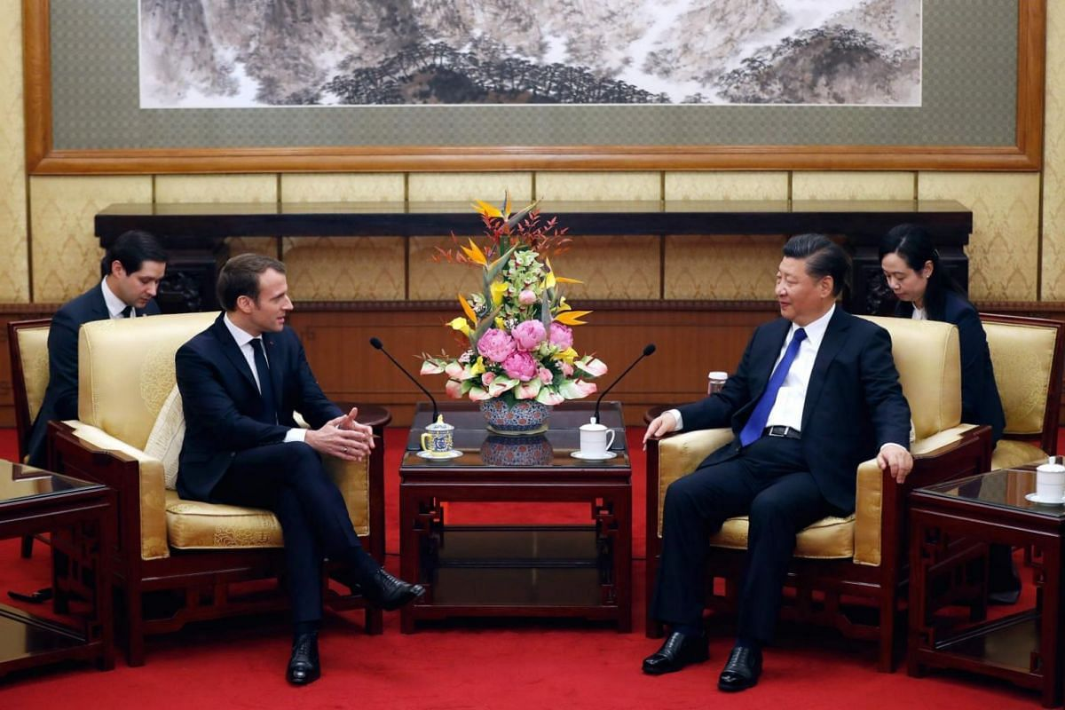 French President Emmanuel Macron chats with Chinese President Xi Jinping during a meeting at the Diaoyutai State Guesthouse in Beijing on Jan 8.