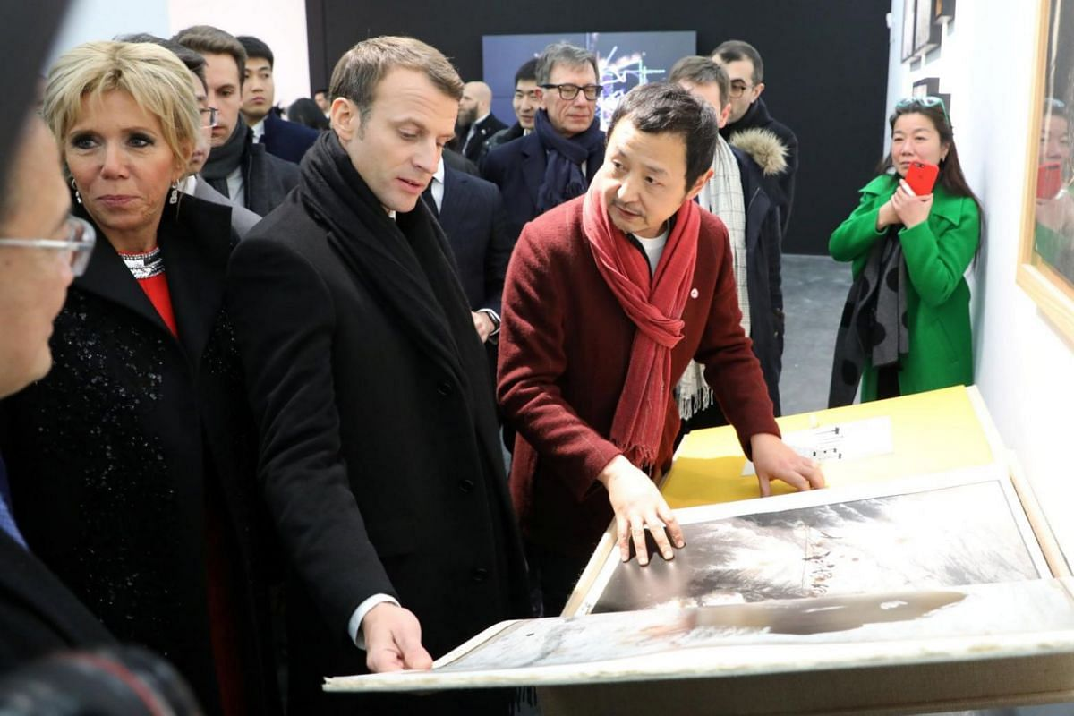 French president Emmanuel Macron and his wife Brigitte chat with photographer Gao Bo during a visit to the Ullens Chinese Contemporary Art Centre in Beijing on Jan 9.