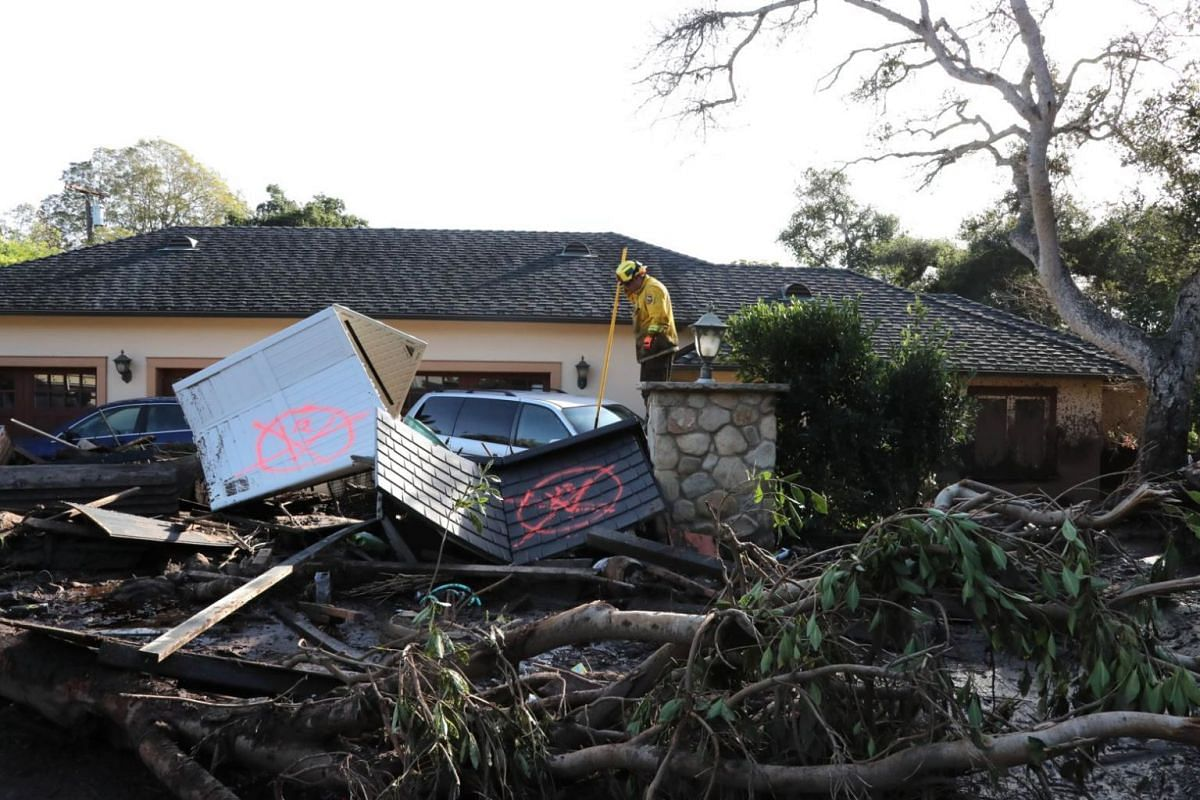 A firefighter conducts search and rescue at a home after heavy rains caused deadly mudslides in Montecito, California.