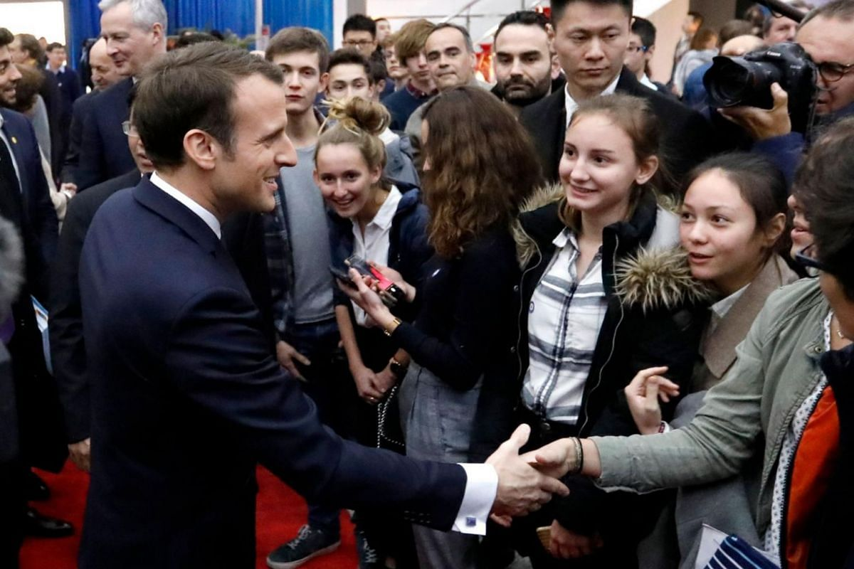 French president Emmanuel Macron shakes hands with high school students during a visit to the China Academy of Space Technology on Jan 10.