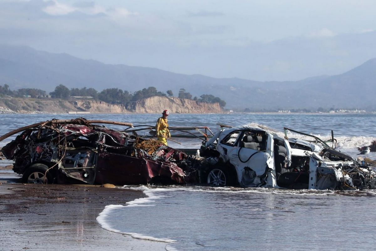 Fremont City Firefighter Jordan Castro checks vehicles that had been washed into the Pacific Ocean as he conducts search and rescue in Montecito, California.