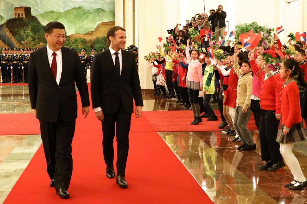 French president Emmanuel Macron and Chinese President Xi Jinping are greeted by children during a welcome ceremony at the Great Hall of the People in Beijing on Jan 9.