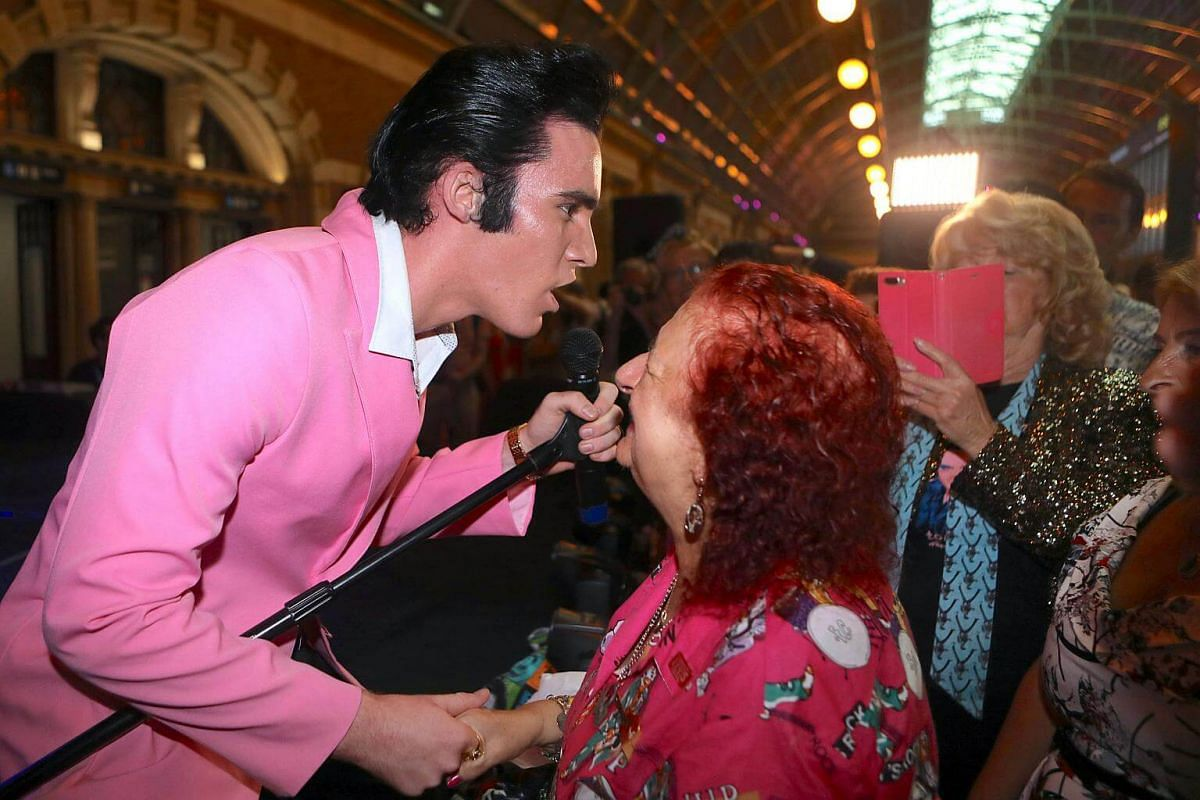 Elvis Presley impersonator Brody Finlay greets onlookers before boarding the Elvis Express train at Sydney's Central station before it departs for the 26th annual Elvis Festival in Parkes, Australia, on Jan 11, 2018.