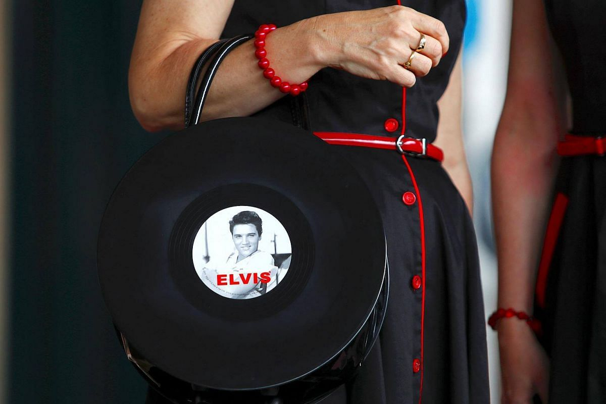An Elvis Presley fan holds a handbag as she prepares to board the Elvis Express train at Sydney's Central station before it departs for the 26th annual Elvis Festival in Parkes, Australia, on Jan 11, 2018.
