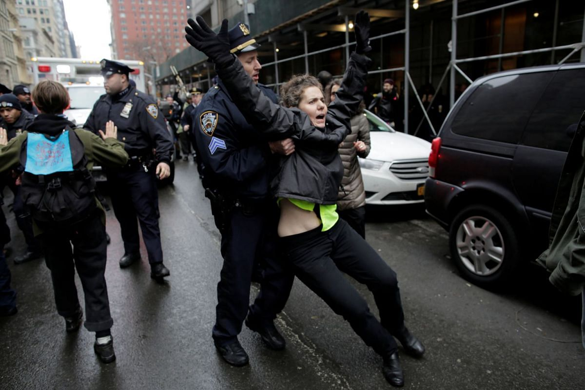 An activist is detained as protestors clashed with police during a demonstration against deportation outside the Jacob Javits Federal Building in Manhattan in New York City, U.S., January 11, 2018. PHOTO: REUTERS