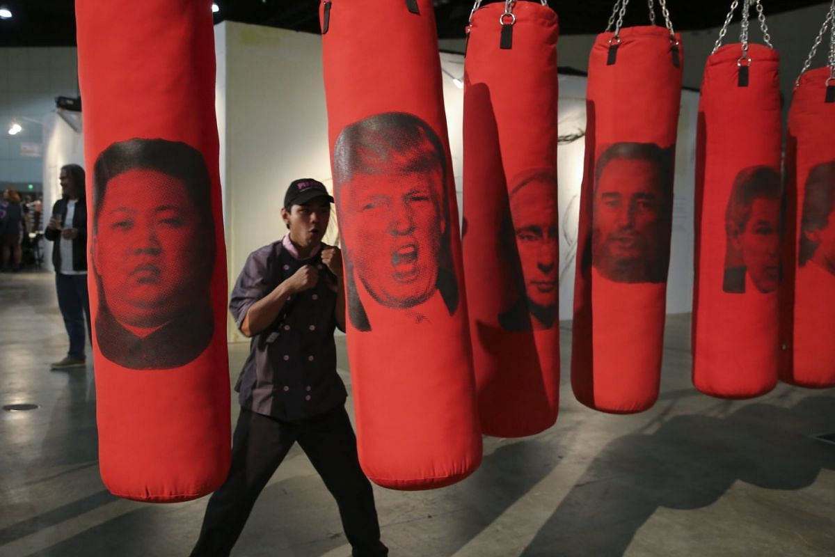 A visitor hits a punching bag bearing an image of US president Donald Trump among other world leaders as part of an installation artwork entitled 'Left or Right' during the opening of the LA Art Show in Los Angeles, California, USA, January 10, 2018.