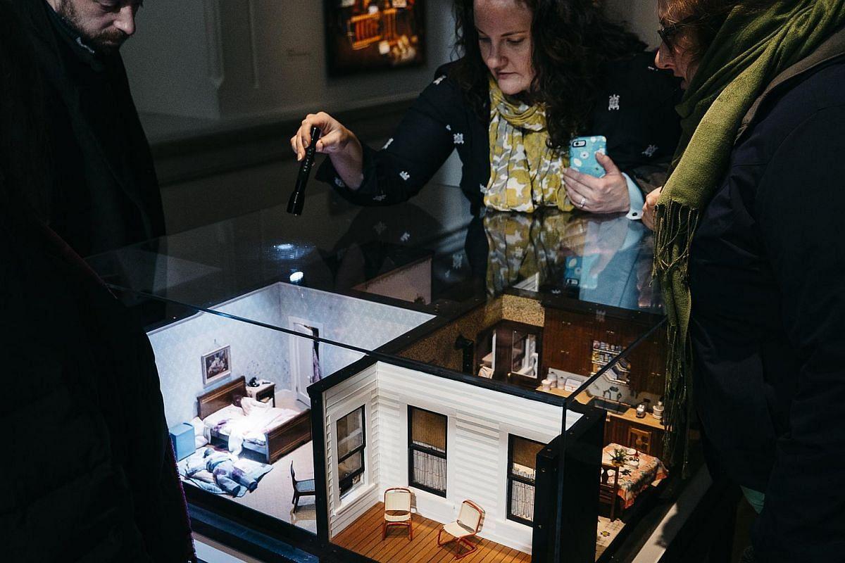 Visitors examine the Three-Room Dwelling exhibit.