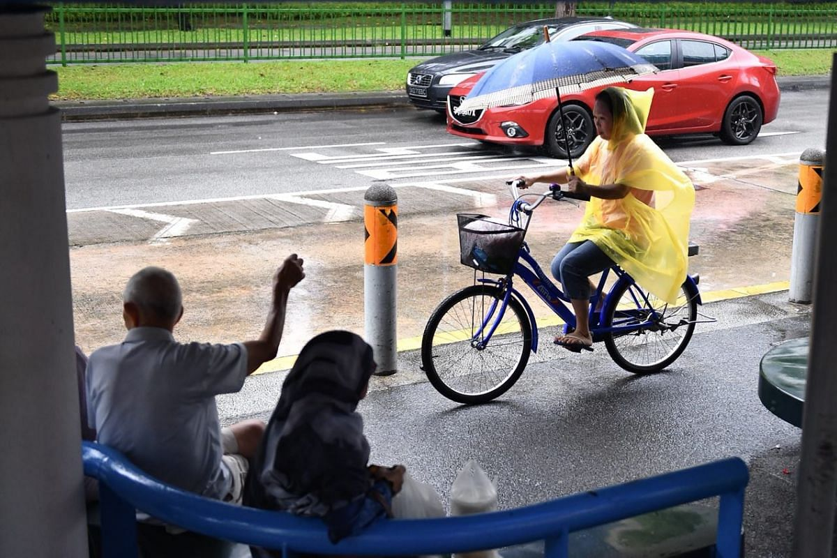 A cyclist with a poncho and umbrella at the bus stop near Blk 442 Pasir Ris Drive 6 at 10.33am on Jan 12, 2018.