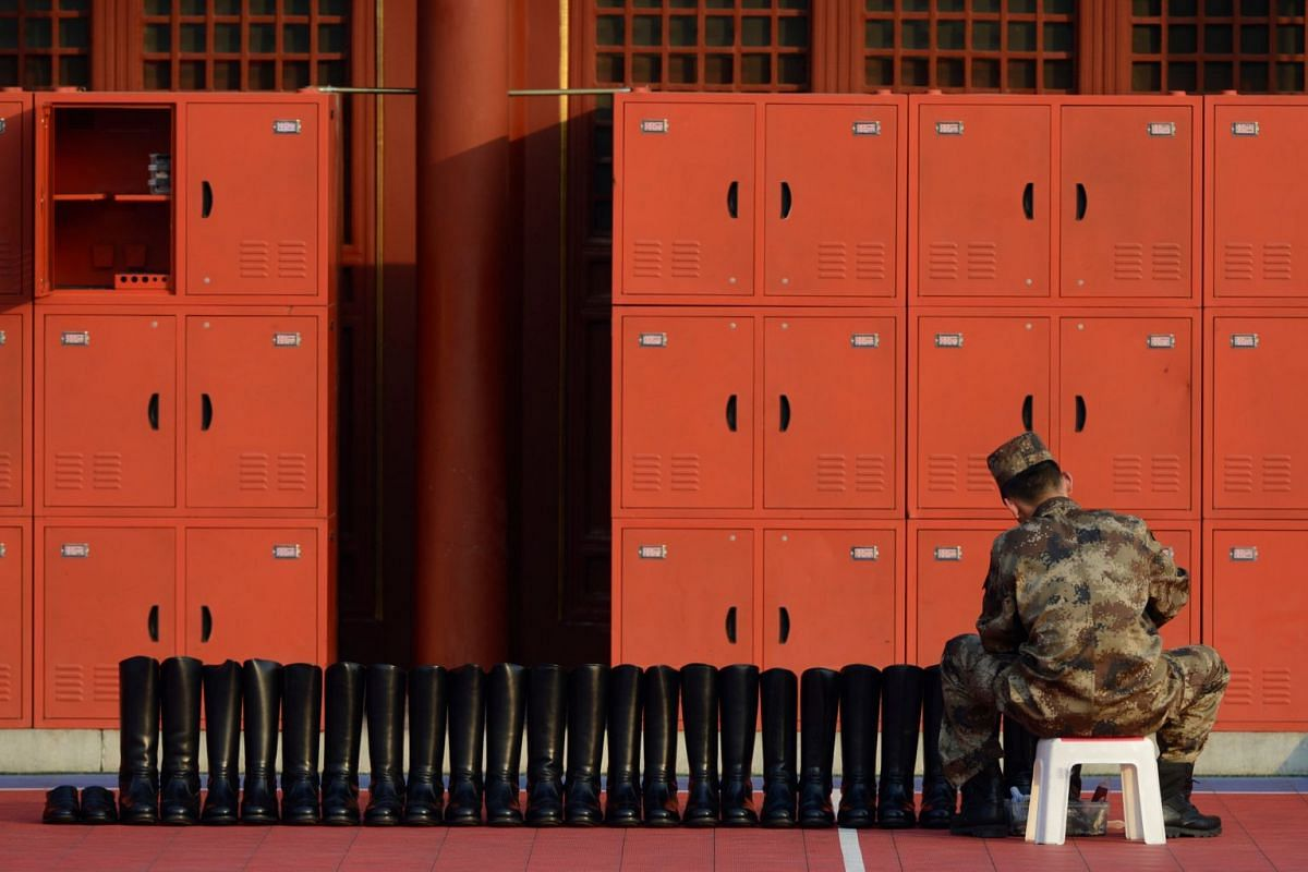 A member of Chinese People's Liberation Army (PLA) cleans boots before the national flag-raising ceremony in Beijing, China January 14, 2018.