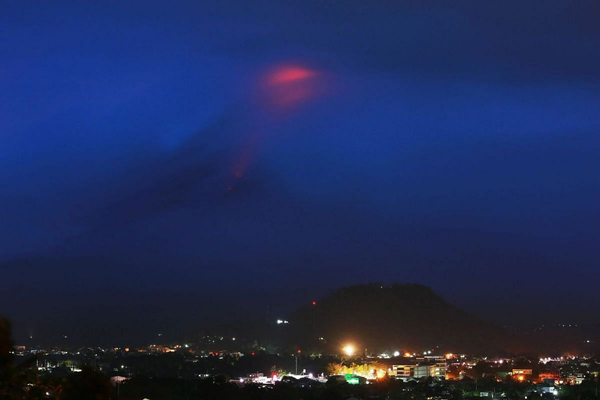 The glow (at top) of lava from the cloud-covered Mayon volcano as it erupts is pictured from the Philippine city of Legazpi in Albay province, early on January 15, 2018. The Philippines raised the alert level for the country's most active volcano twi