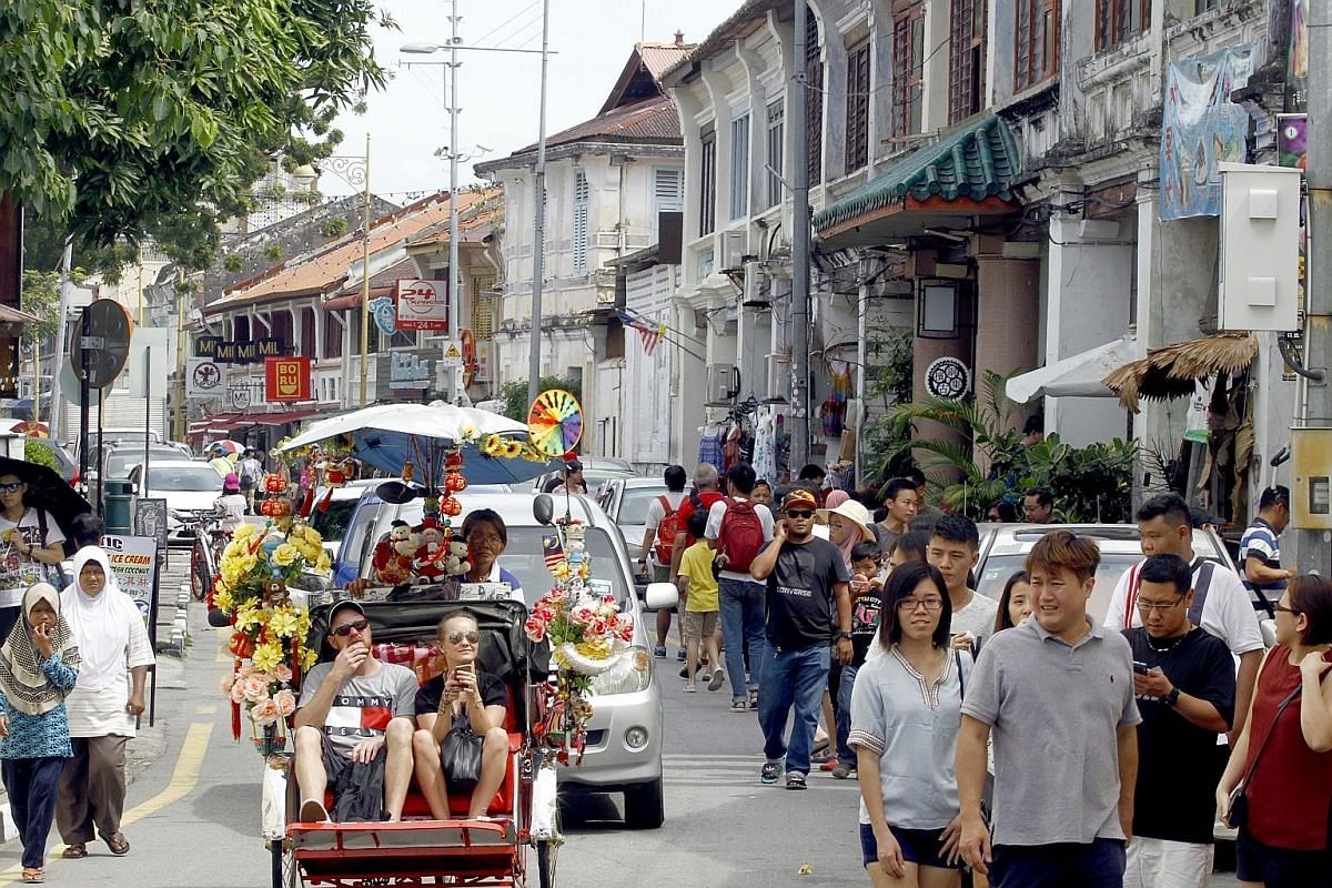 """Tourists exploring Lebuh Cannon, known for its shophouses and clan temples. The culture and traditions that made George Town unique are slowly being replaced by lookalike boutique hotels and """"Instagrammable"""" cafes. Three generations of family members"""