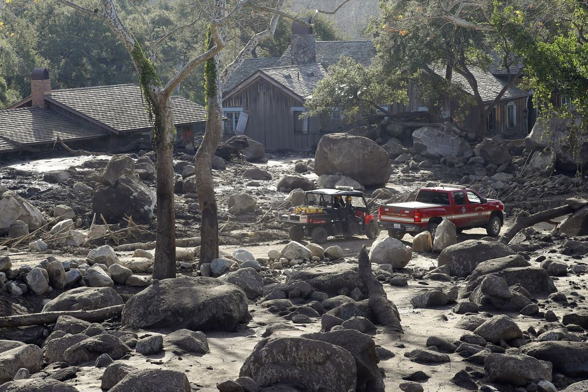 Firefighters amid boulders strewn by the mudslide in a neighborhood in Montecito, California on January 15, 2018.