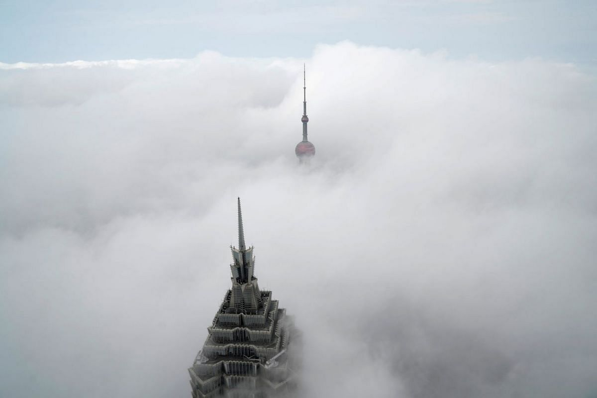 Skyscrapers Oriental Pearl Tower and Jin Mao Tower (L) are seen from the Shanghai World Financial Center on a hazy day in the financial district of Pudong in Shanghai, China, January 16, 2018.
