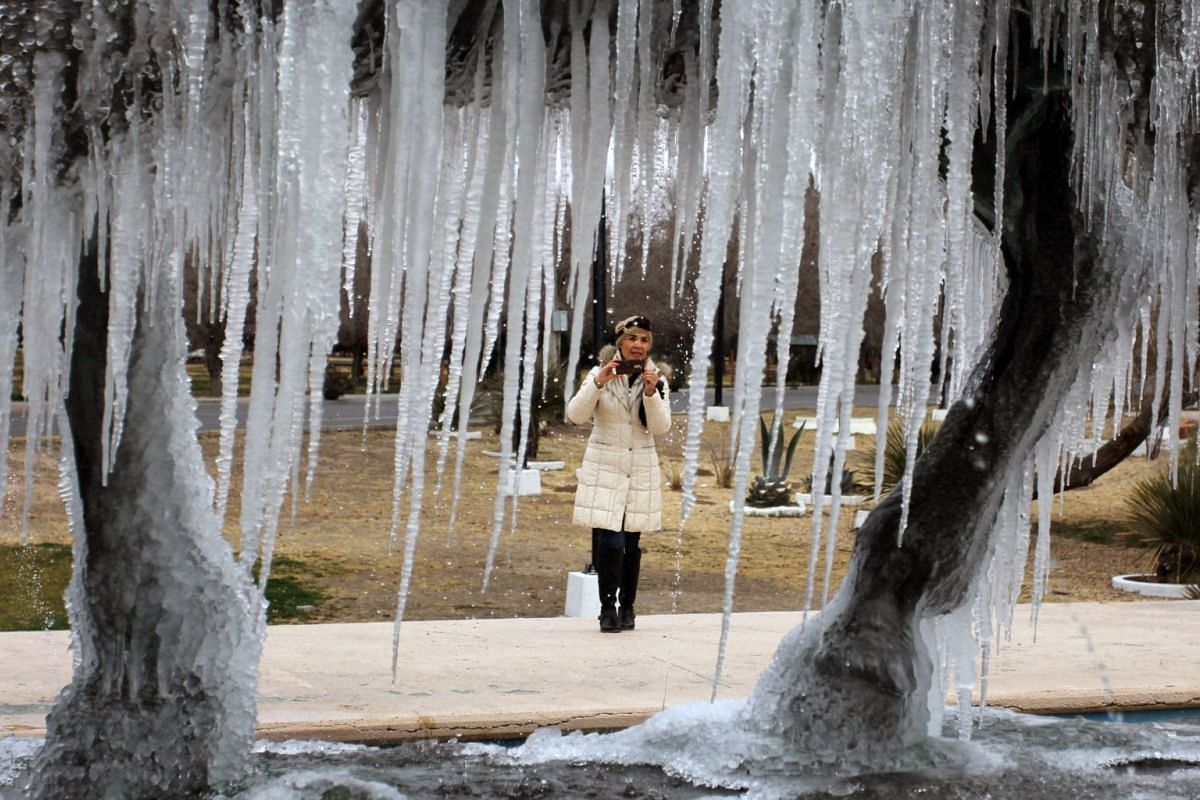 A woman takes a picture of a monument covered with ice, after the decrease in the temperature in Ciudad Juarez, Chihuahua state, Mexico on January 16, 2018.