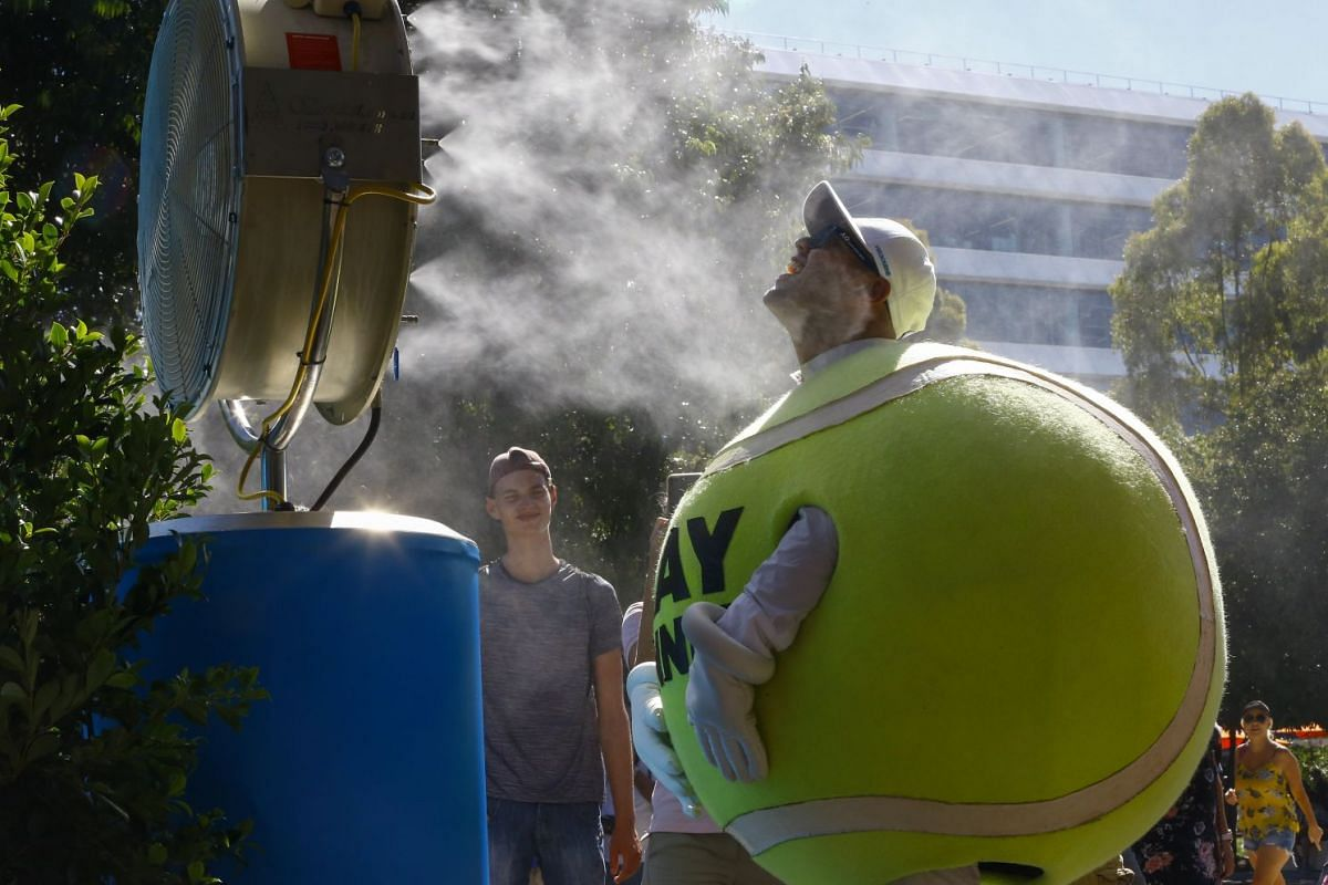 Promotion staff cool off in mist sprayed by a water misting fan on a hot summer day at the Australian Open tennis tournament in Melbourne, Australia, on January 18, 2018.