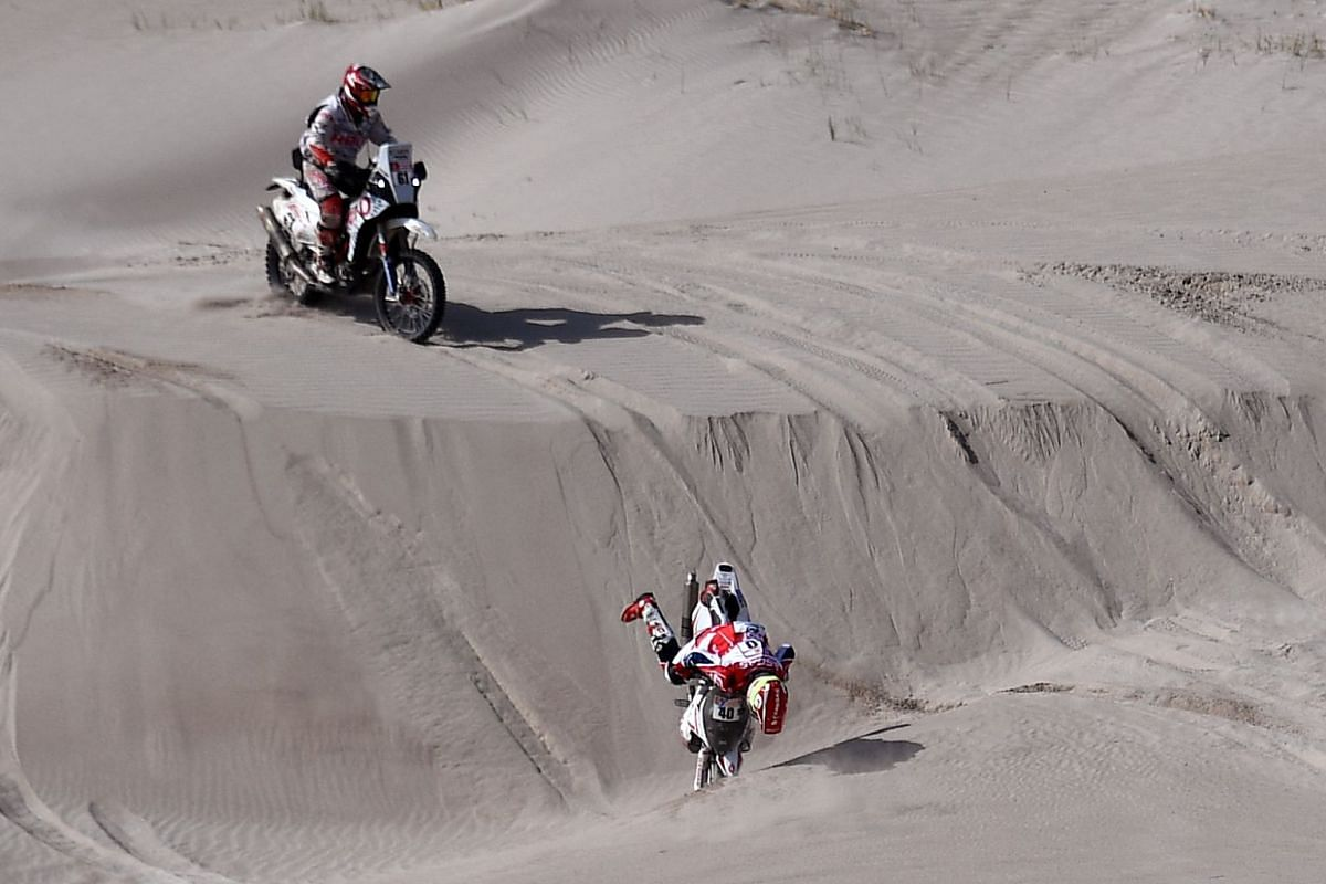 French rider Johnny Aubert falls in front of Spanish biker Oriol Mena, during the Stage 11 of the 2018 Dakar Rally between Belen and Chilecito, in Argentina, on January 17, 2018.