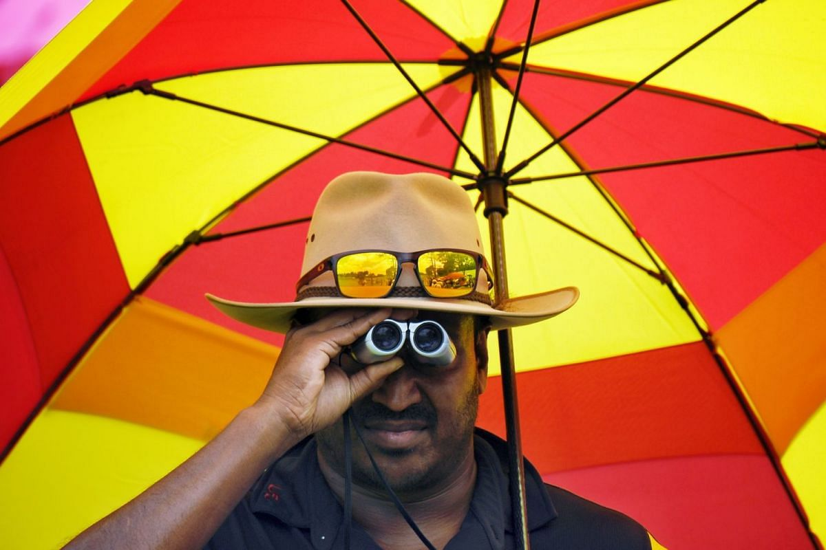 A spectator using binoculars to watch the action on the first day of the SMBC Singapore Open.