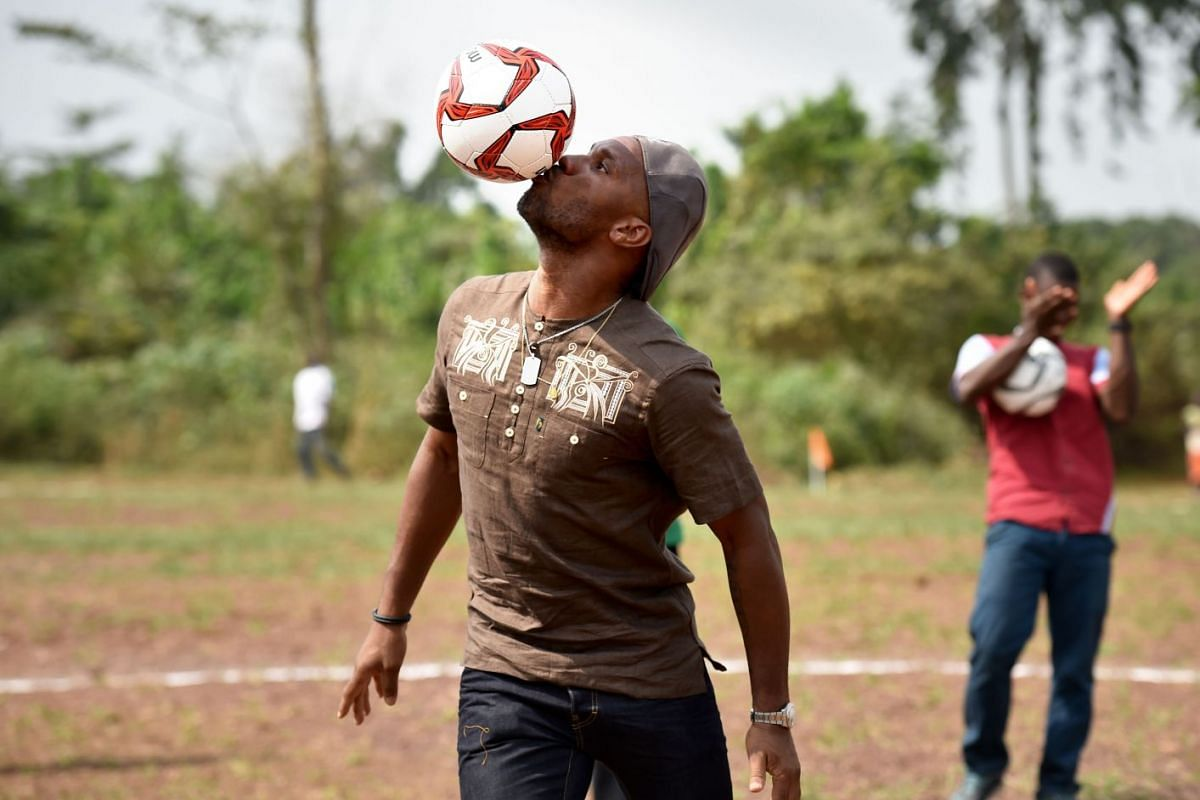 Ivory Coast's football star Didier Drogba plays with a ball on the football ground of the Primary School Didier Drogba during its inauguration on January 17, 2018 in Pokou-Kouamekro, near Gagnoa, central-western Ivory Coast. Didier Drogba sponsored t