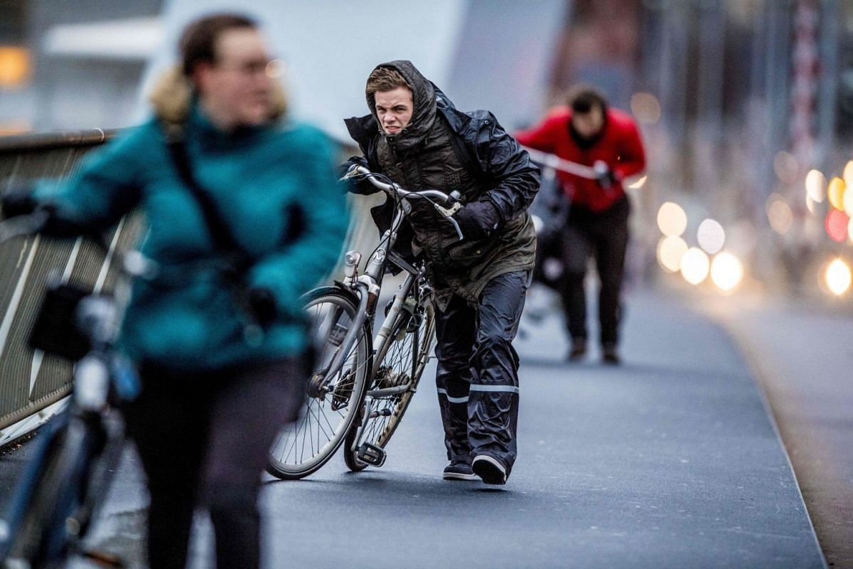 People walk with a bicycle through fierce winds in Rotterdam during the second western storm of the year. The Royal Netherlands Meteorological Institute (KNMI) has issued a code red for the storm that is expected to bring wind speeds up to 140 kph.