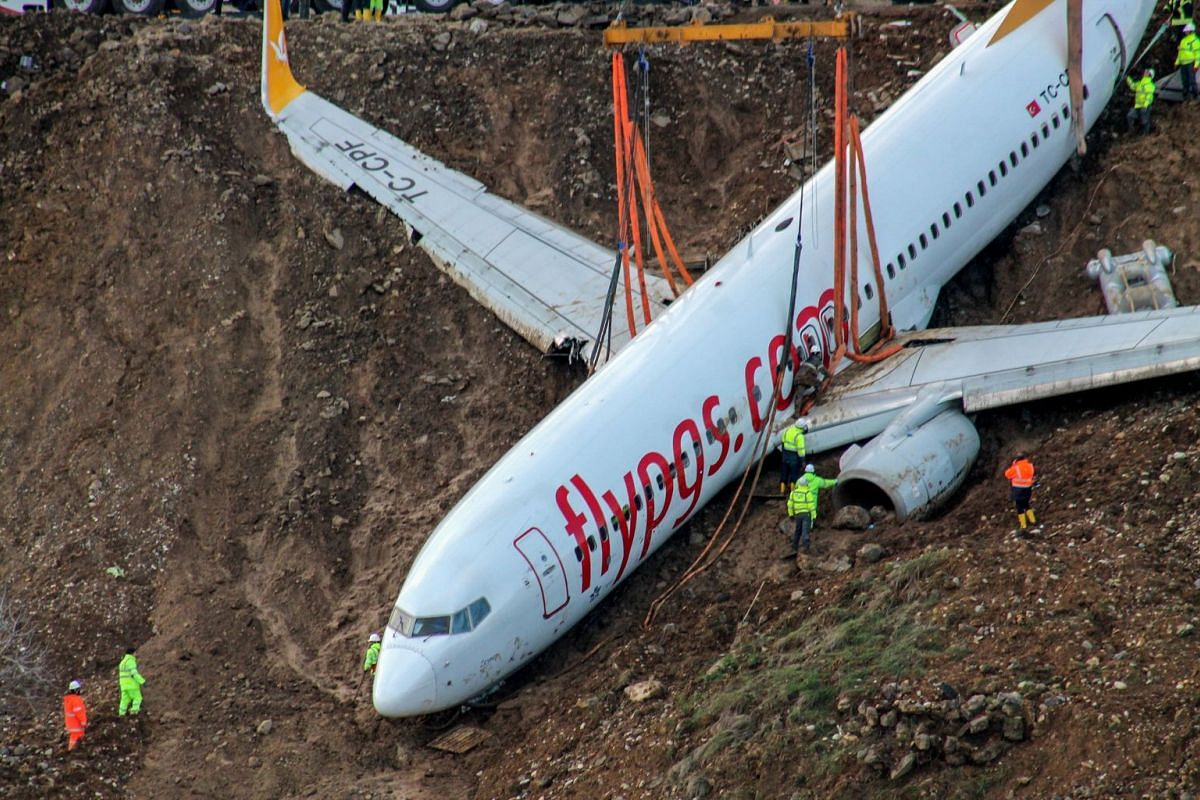 Technicians look on on January 18, 2018 as cranes lift the Pegasus airplane which skidded off the runway after landing in Trabzon Airport on January 15, 2018. A Turkish passenger plane that plunged off a runway onto a cliff precariously close to the