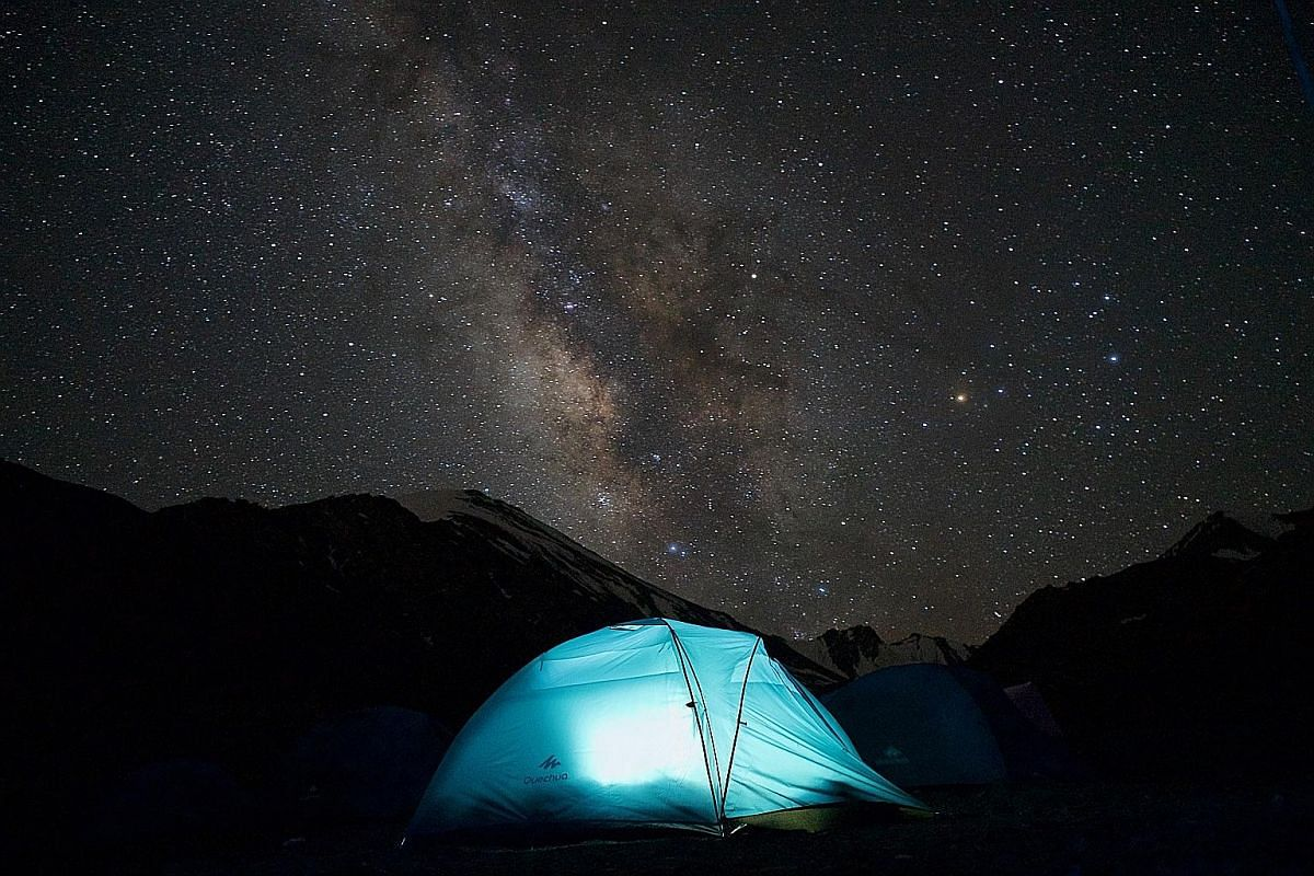 (Left) The Milky Way illuminates the night sky at the base camp of Stok Kangri. (Right) Writer Oscar Boyd and his climbing companion Anna reach the summit of Stok Kangri at 6,153m above sea level. The ascent of Stok Kangri, in the background, takes t