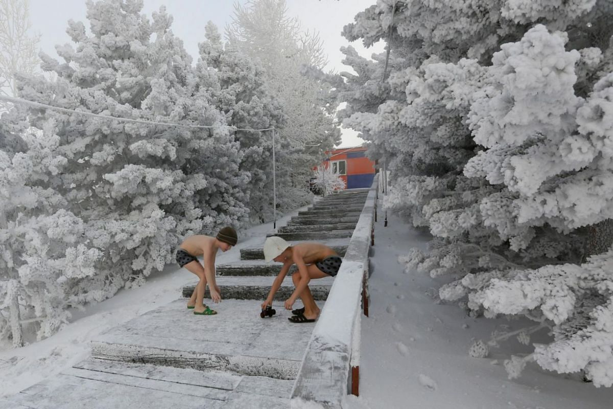 Seven-year-old twins brothers Miroslav and Timophei Yaroshenko, members of the Cryophile winter swimmers club, play on a bank the Yenisei River that has been covered in snow, with the air temperature at about minus 38 deg C on Jan 21, 2018.